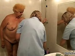 Old mature is having a shower when caregiver cleans her