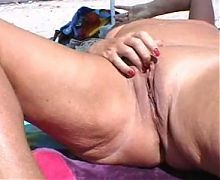 Mature masturbating naked on the beach